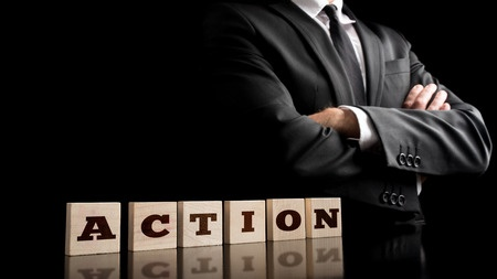 42851664 - businessman in a strong confident pose standing next to six wooden cubes spelling action in a conceptual image of business vision and determination.